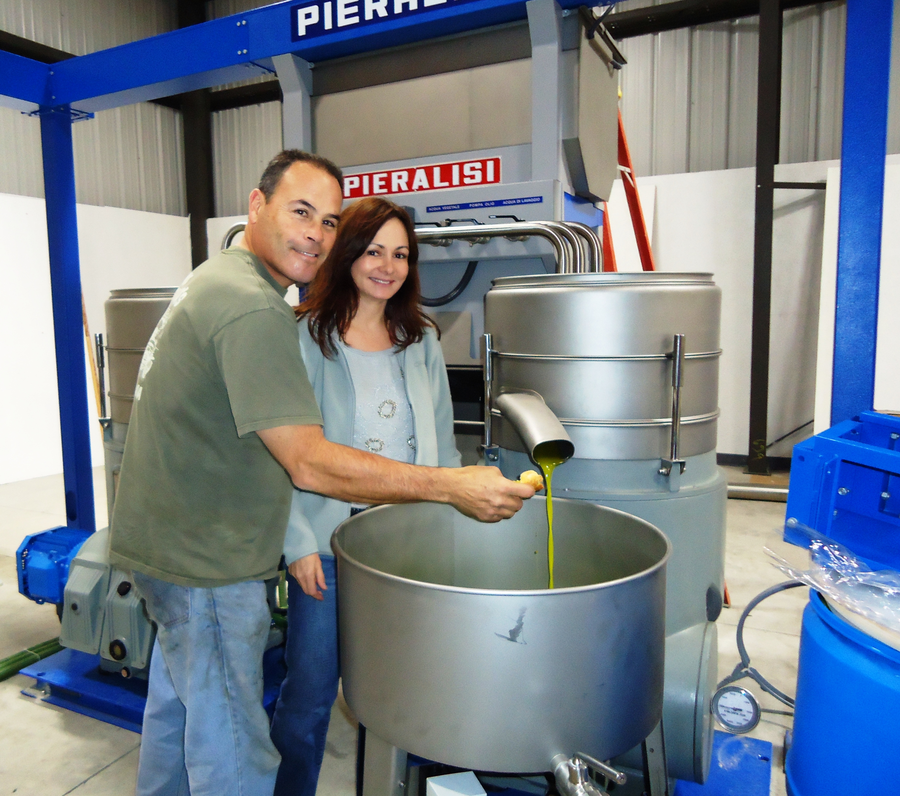 Frank and Marti Menacho taste their fresh olive oil in production.